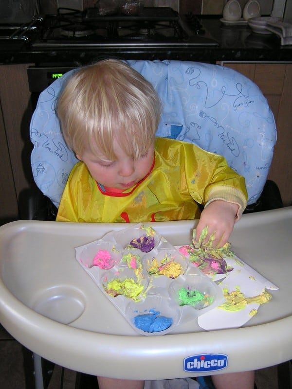 toddler in high chair finger painting