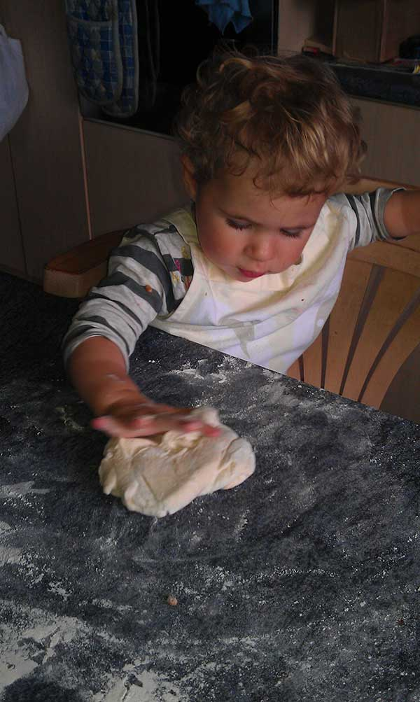 Toddler kneading pizza dough at the kitchen table.