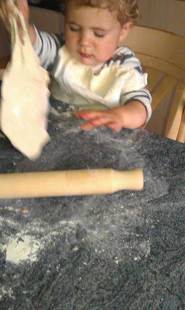 Toddler sitting at the table working the dough