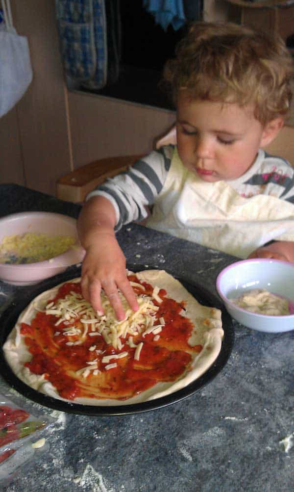 Toddler adding toppings to a homemade pizza base