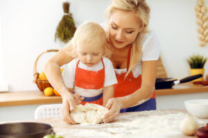 mum and toddler making pizza dough and dividing up together