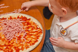 toddler adding toppings to a pizza base