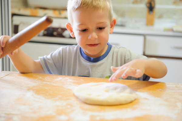 toddler rolling out pizza dough