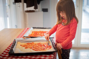 toddler spreading sauce over pizza bases
