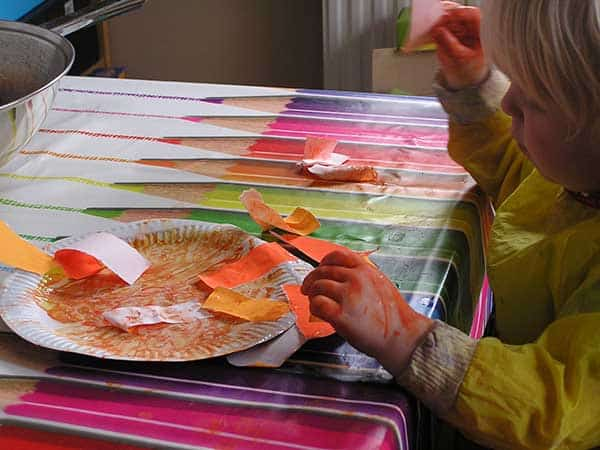 Adding the mane to a paper plate lion a simple craft for toddlers and you to do together