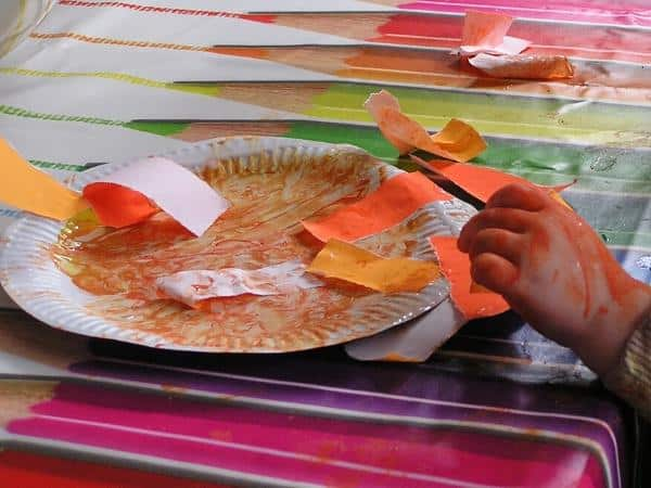 adding torn paper to a paper plate