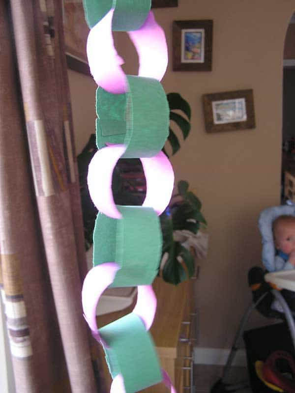 Easy Halloween Paper Chain made with a toddler using purple and green construction paper.