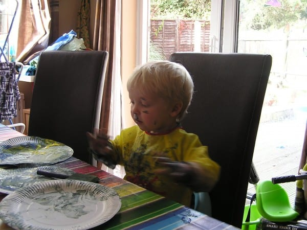 Toddler painting in a booster seat at the table