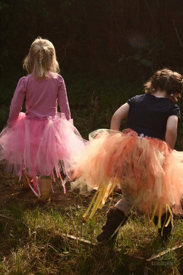 girls playing in the garden hunting fairies with homemade tutus on