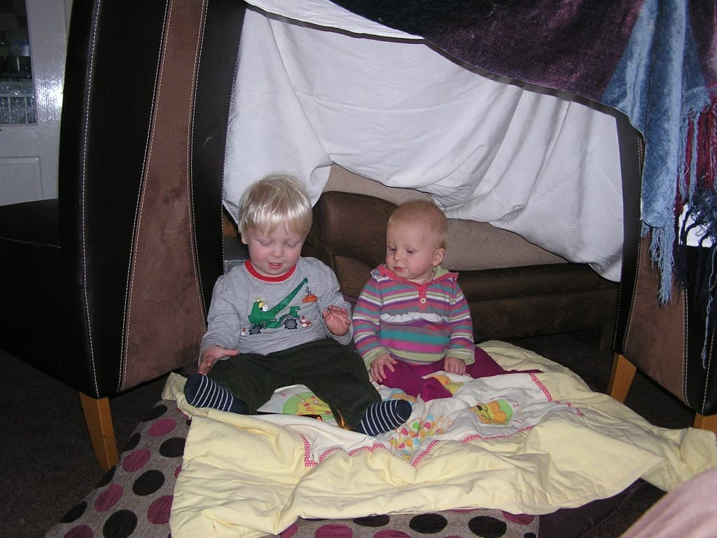 baby and toddler in a homemade den after heading off on a pretend bear hunt