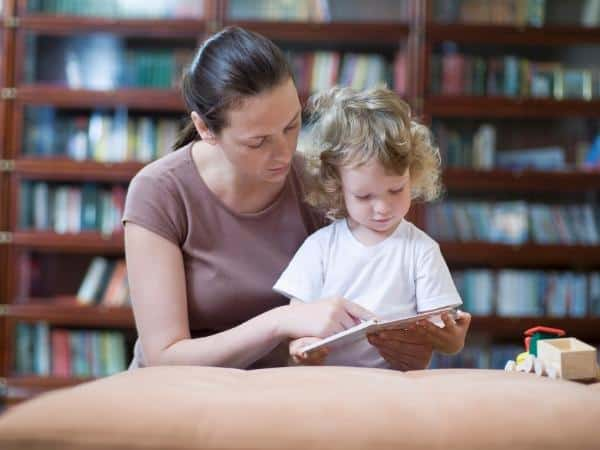 mother and toddler reading at the library together