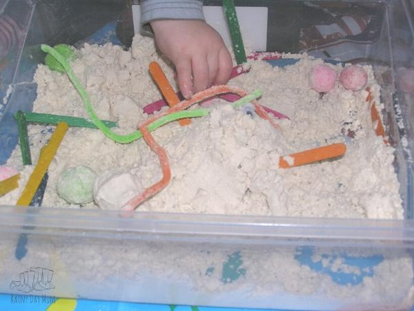 playing in a sensory bin filled with cloud dough pretending it is snow