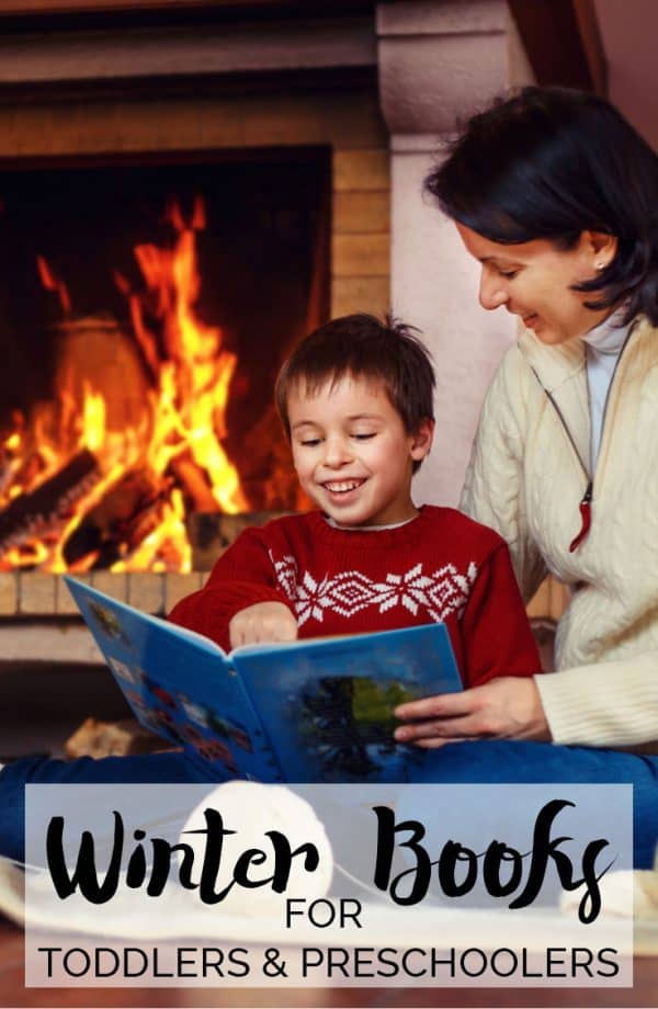 mum and son reading winter books by the fireplace