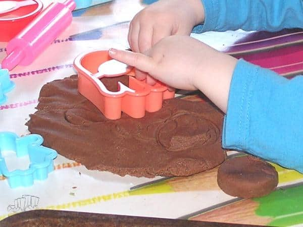 toddler playing with chocolate playdough made at home