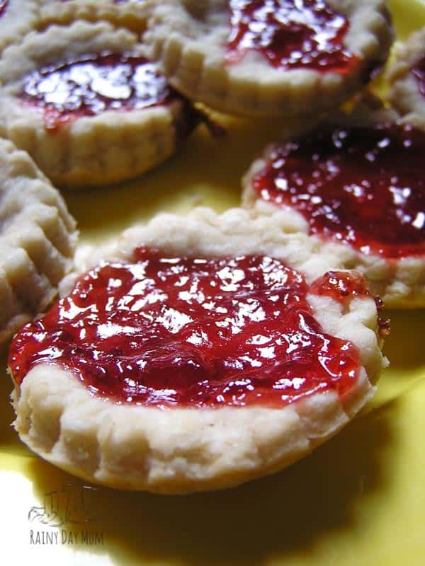 close up of a jam tart cooked by a mom with her toddler in the home kitchen