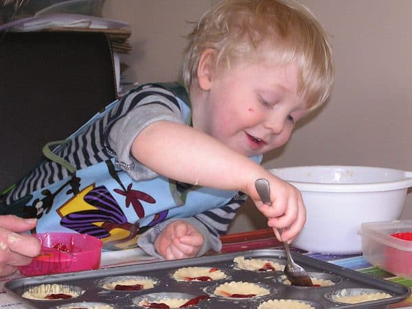 toddler adding jam to jam tarts