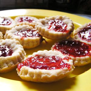 jam tarts made by kids on a yellow plate filled with strawberry jam a quick and easy bake