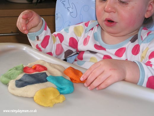 Baby playing with homemade play dough on a high chair tray