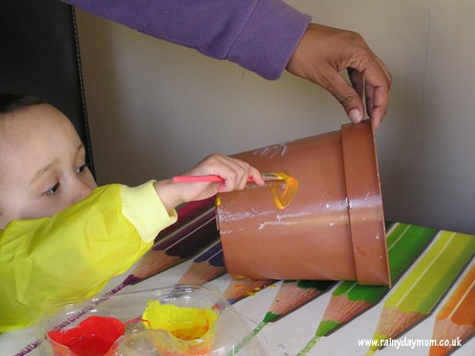 Toddler decorating a pot for sunflowers