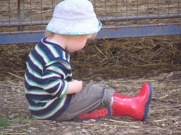 toddler sitting in the mud at the farm