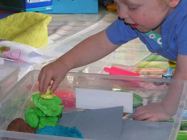 toddler playing at home in a quick and easy sensory bin retelling a nursery rhyme