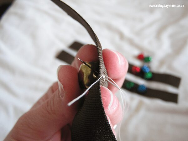 Sewing on a bell onto the ribbon