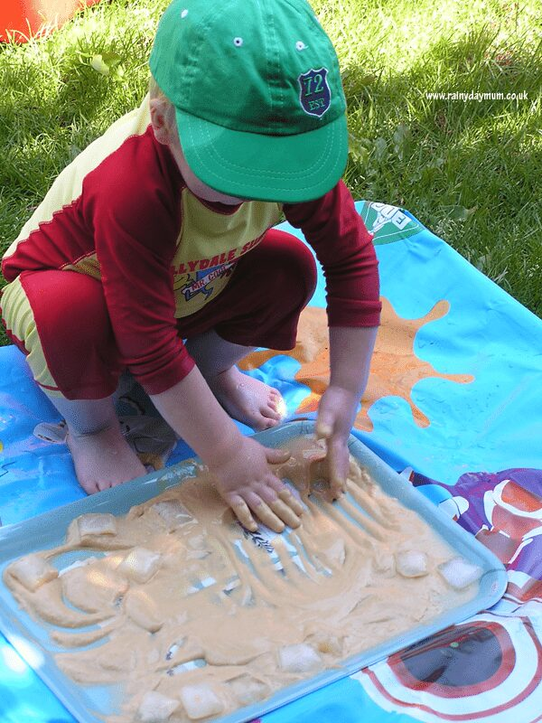 child playing with ice and pudding mix in the garden