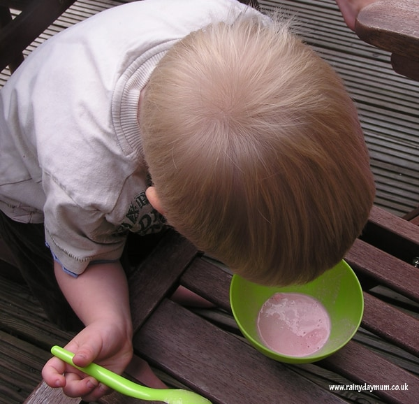 preschooler keeping a close eye on a bowl of ice cream melting in the shade as part of a simple summer science experiment.