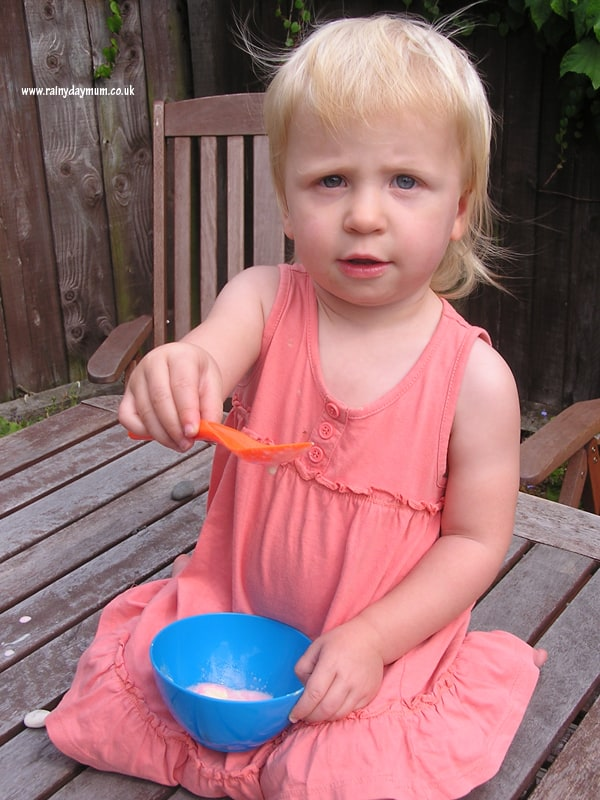 toddler sitting on a table eating an edible science experiment exploring melting with ice-cream
