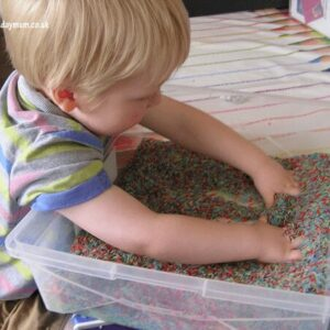 mixing up colours in rice sensory tub