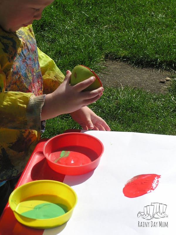 toddler making prints with a cut apple