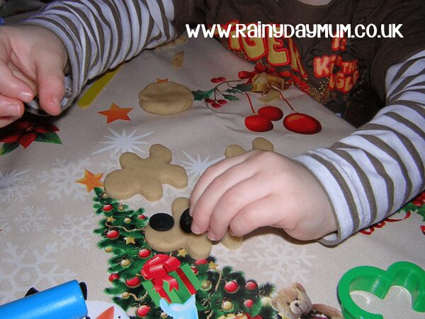 child playough with gingerbread playdough on a christmas table mat adding buttons to play doh gingerbread men