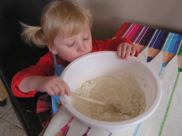 toddler mixing together the soda bread dough in a bowl