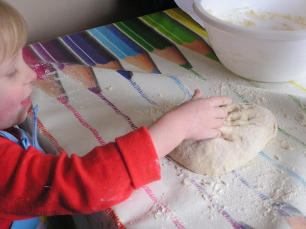 toddler kneading the bread dough