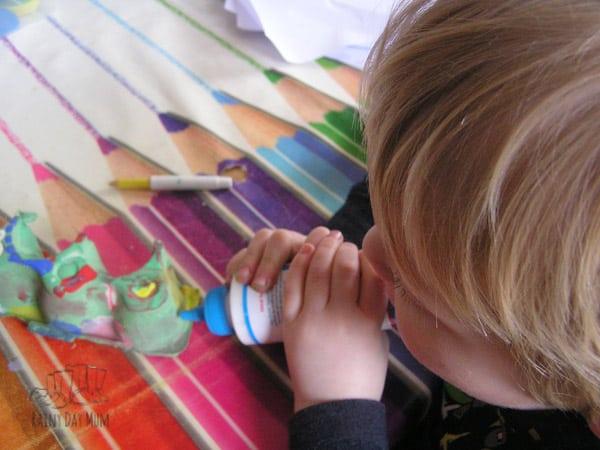 preschooler using glue in a spring craft