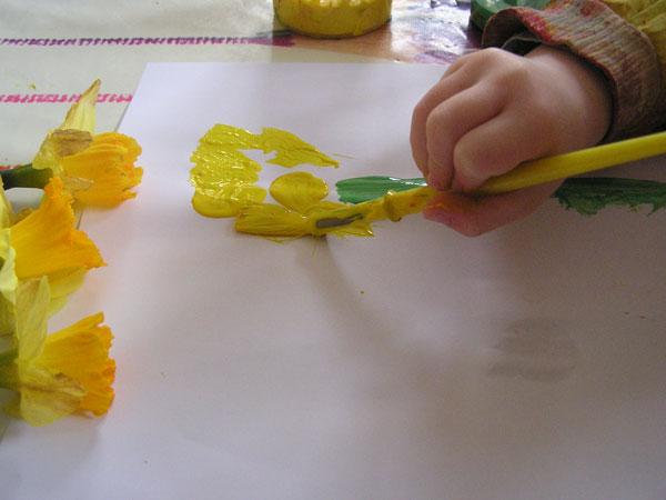 preschooler adding petals to a still life picture of daffodils he has produced