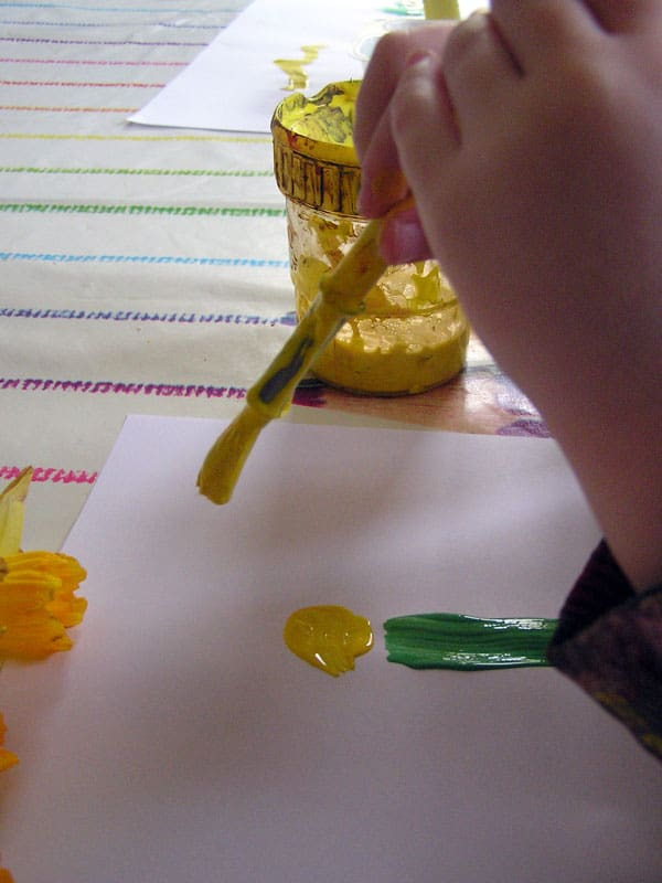 preschooler painting a daffodil. strokes and dot for the stem and centre of the flower.