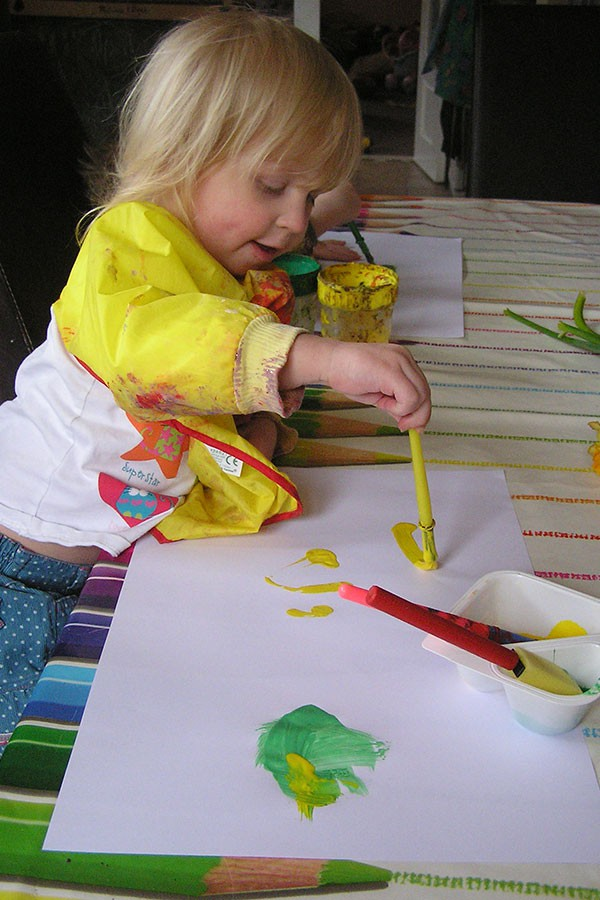 Toddler creating pictures of daffodils