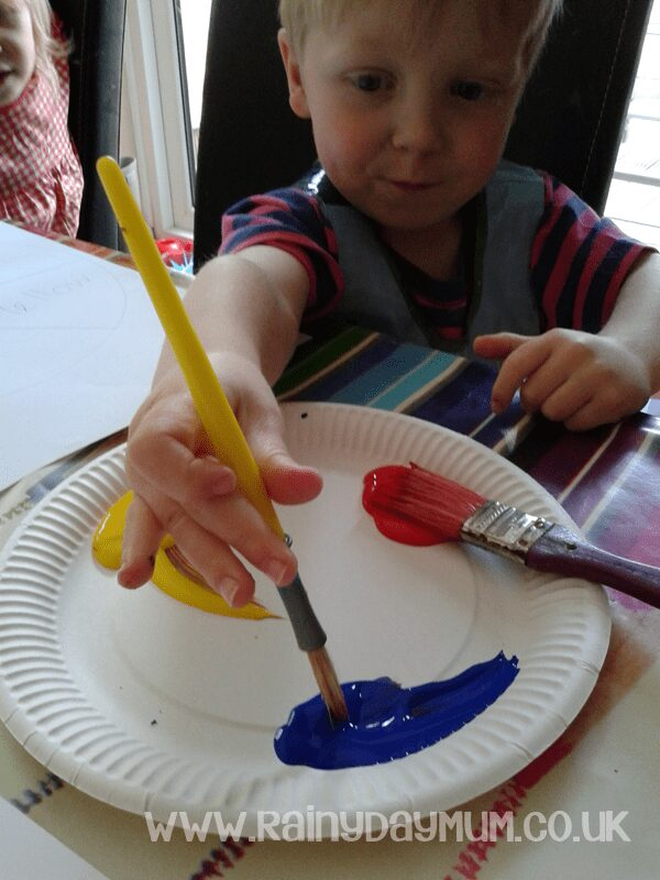 mixing primary paint colours on a paper plate