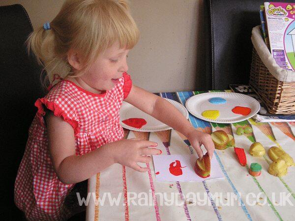 toddler making potato proints