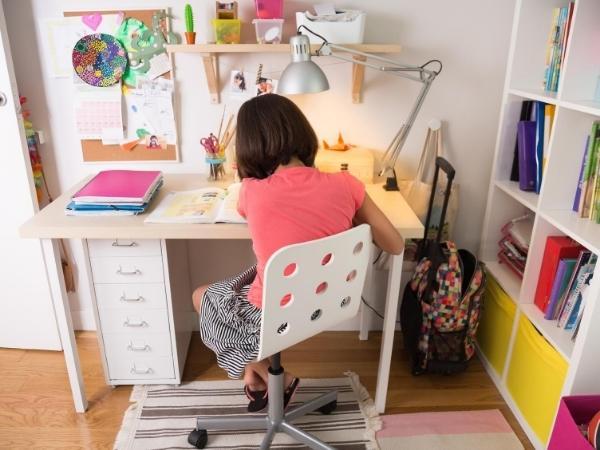 girl doing home learning at her desk in her bedroom