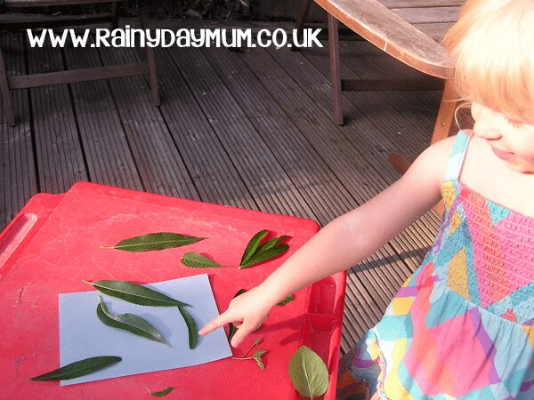 preschooler making sun prints with nature objects