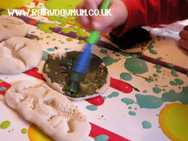 child painting a salt dough fossil to look more rock like