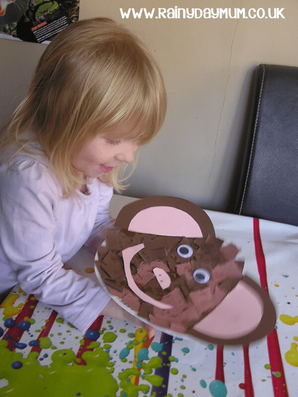 preschooler holding a paper plate monkey that she has created