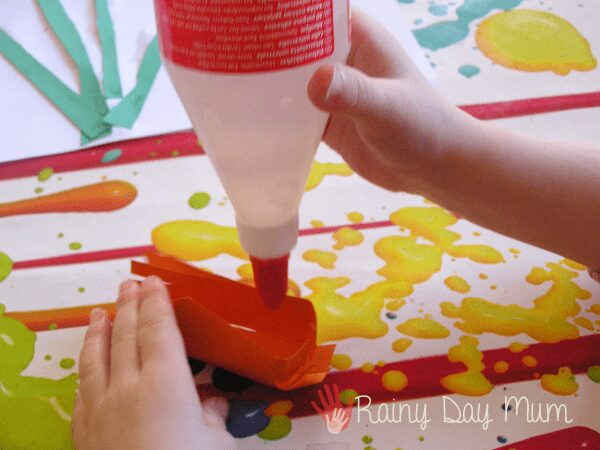 preschooler gluing paper using a liquid glue