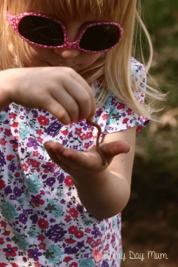 girl holding a worm in her hands