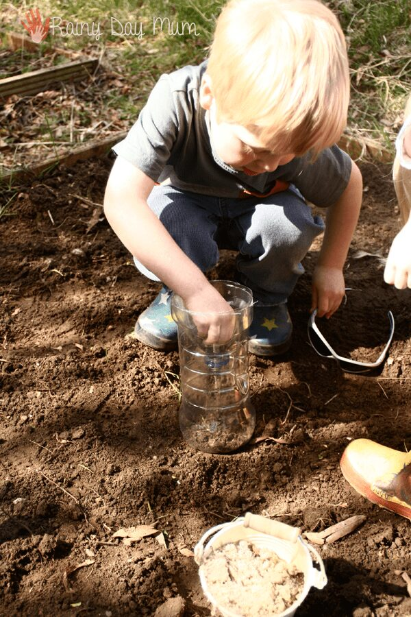 filling a plastic bottle with sand and soil to form layers