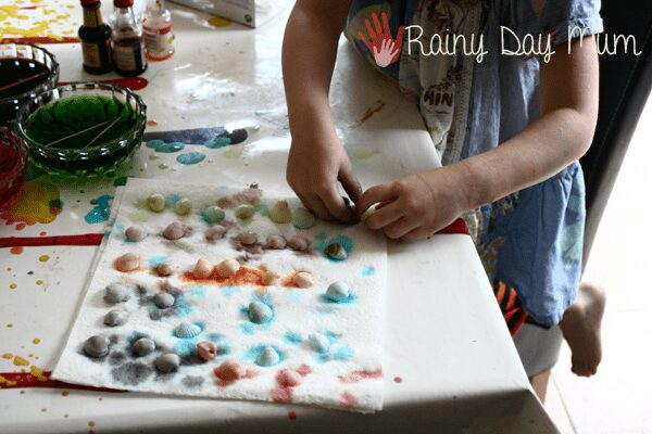 preschoolers taking out sea shells that have been dyed and placing on paper towel to dry
