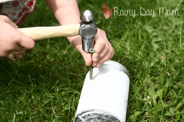 child punching holes in a tin can to create a lantern with a hammer and a screw