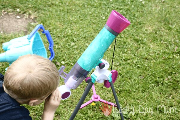 child looking through a telescope up at the moon during the day to see the craters and other features.